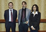 Photo of two men and one woman posing for a picture. The man in the center is holding an award.