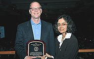 Photo of one man and one woman posing for a picture. The man is holding an award.
