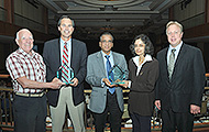 Photo of four men and one woman posing for a group picture. Two of the men are holding awards.
