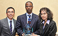 Photo of two men and one woman posing for a group picture. One of the men is holding an award.